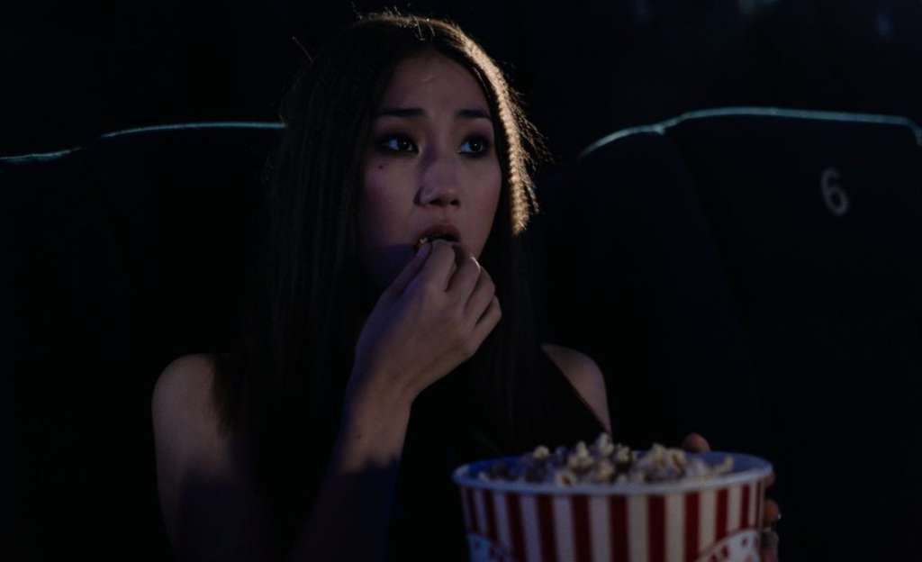 photo of a woman eating popcorn at a movie theater